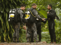 Australian Federal Police and Defense Force personnel talk to a Thai rescuer, right, before diving after the 12 boys and their soccer coach were found alive, in Mae Sai, Chiang Rai province, in northern Thailand, Tuesday, July 3, 2018. The 12 boys and soccer coach found after 10 days are …