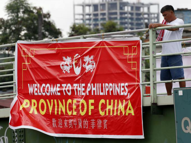 """Red tarpaulin banners with the words, in English: """"Welcome to the Philippines, Province of China"""" mysteriously appeared on footbridges across the capital, Manila, on Thursday."""