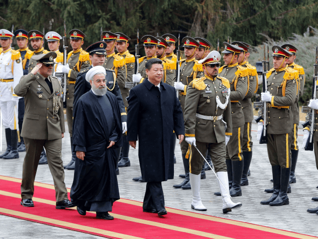 Iranian President Hassan Rouhani and Chinese President Xi Jinping (R) review troops during a welcoming ceremony on January 23, 2016 in the capital Tehran. Chinese President Xi Jinping arrived on January 22, 2016 in Iran on the third leg of a Middle East tour aimed at boosting economic ties with …