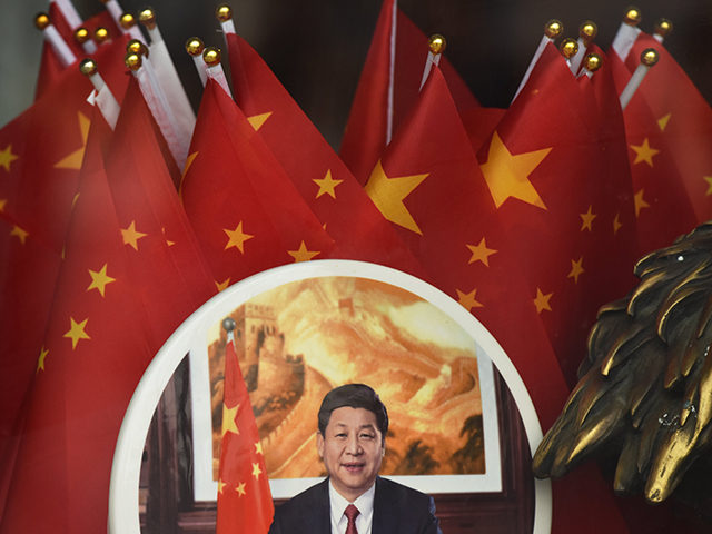 A decorative plate featuring an image of Chinese President Xi Jinping is seen in front of Chinese flags at a souvenir store next to Tiananmen Square in Beijing on February 27, 2018. China's propaganda machine kicked into overdrive on February 27 to defend the Communist Party's move to scrap term …