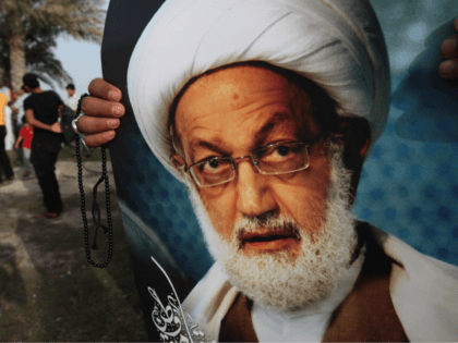 A Bahraini anti-government protester holds a poster of top Shiite cleric Sheik Isa Qassim during a demonstration Friday, May 17, 2013, in Karrana, Bahrain, just outside the capital of Manama. A main opposition group in Bahrain says police have searched the home of Qassim, who has strongly sided with anti-government …