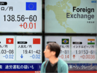 A pedestrian walks past a foreign exchange rate board, including the euro (top,L) and the Chinese yuan (bottom, L) in Tokyo on August 13, 2015. Tokyo stocks closed 0.99 percent higher August 13, rallying after the previous day's losses as investors gauged the impact of China devaluing its currency for …