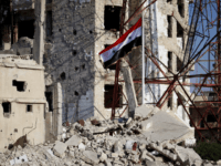 The Syrian national flag rises in the midst of damaged buildings in Daraa-al-Balad, an opposition-held part of the southern city of Daraa, on July 12, 2018. - Syria's army entered rebel-held parts of Daraa city , state media said, raising the national flag in the cradle of the uprising that …