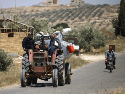 Syrians displaced by government forces' bombardment in the southern Daraa province countryside drive near the town of Shayyah, south of the city of Daraa, towards the border area between the Israeli-occupied Golan heights and Syria on June 29, 2018. (Photo by Mohamad ABAZEED / AFP) (Photo credit should read MOHAMAD …