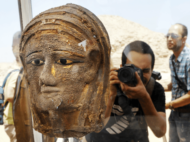 A photographer films a gilded silver mummy mask found on the face of the mummy of the second priest of Mut, as it is displayed during a press conference in front of the step pyramid of Saqqara, in Giza, Saturday, July 14, 2018. Archaeologists say they have discovered a mummification …