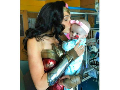This image released by Kelly Swink Sahady shows Gal Gadot, dressed as Wonder Woman kissing Sahady's daughter Karalyne during a visit to Inova Children's Hospital in Falls Church, Va. Gadot signed autographs and posed for photos with patients and staffers and they posted some of the pictures to social media. …
