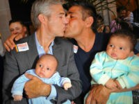 Chris Roe (L) and Roby Chavez (R) celebrate while holding their soon-to-be adopted children as the US Supreme Court ruling is announced on June 26, 2013. The US Supreme Court struck down The Defense of Marriage Act (DOMA) today, and declared that same-sex couples who are legally married deserve equal …