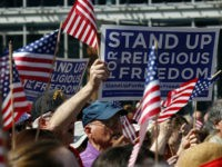 Flags and signs are held during a rally for religious freedom organized in part by the Catholic Archdiocese of Philadelphia in front of Independence Hall Friday, March 23, 2012 in Philadelphia. The rally was in objection to the Health and Human Service mandate that private health care cover women's contraception. …