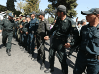 Iranian police stand between supporters of the Basiji militia and supporters of Iranian president Hassan Rouhani upon his arrival from New York, on September 28, 2013 in Tehran. Some 60 hardline Islamists chanted 'Death to America' and 'Death to Israel' but they were outnumbered by 200 to 300 supporters of …