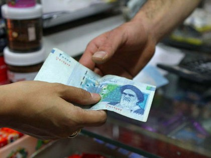An Iranian woman pays a 20000 rial banknote (around 70 US Cent), bearing a portrait of Iran's late founder of islamic Republic Ayatollah Ruhollah Khomeini, to a grocer in Tehran on September 30, 2012. Iran's currency, the rial has lost over 60 percent of its value since the end of …