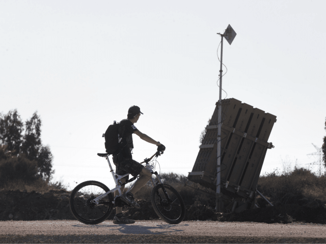 TEL AVIV, ISRAEL - AUGUST 31: (ISRAEL OUT) An Israeli man rides his bicycle past the 'Iron Dome' missile defense system as it is deployed on August 31, 2013 in Tel Aviv, Israel. Tensions are rising in Israel amid international talks of a military intervention In Syria. (Photo by Uriel …