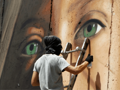 Italian artist Jorit Agoch paints a mural depicting jailed Palestinian teenager Ahed Tamimi on Israel's controversial separation barrier in the West Bank city of Bethlehem, on July 25,2018. - Tamimi, was charged earlier this year after a viral video showed her hitting two soldiers in the occupied West Bank. (Photo …