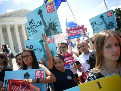 WASHINGTON, DC - JUNE 26: Protesters hols up signs that read 'No Muslim ban' against U.S. President Trump's travel ban gather outside the U.S. Supreme Court as the court issued an immigration ruling June 26, 2018 in Washington, DC. The court issued a 5-4 ruling upholding U.S. President Donald Trump's …