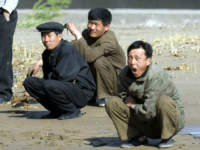 North Koreans squat on mudflats at the North Korean town of Sinuiju, opposite the Chinese city of Dandong Friday April 23, 2004. Despite their countries' ostensible friendship, the mood at the border is tense and dour, and the contrast between China's relative wealth and openness and North Korea's poverty and …
