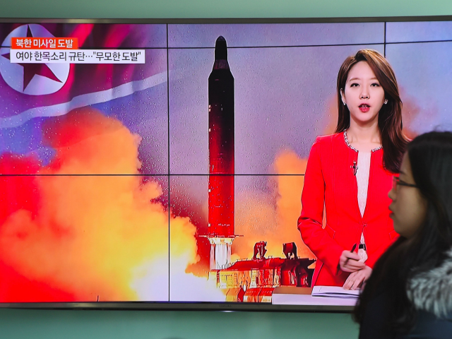 A woman walks past a television screen showing file footage of North Korea's missile launch at a railway station in Seoul on February 12, 2017. North Korea fired a ballistic missile on February 12 in an apparent provocation to test the response from new US President Donald Trump, the South …