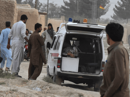 People gather around an ambulance loaded with a dead body following a bomb blast at an election rally in Mastung on July 13, 2018. - A bomb killed at least 70 people and injured 40 others during a rally in Pakistan's restive Balochistan province, in the day's second attack on …
