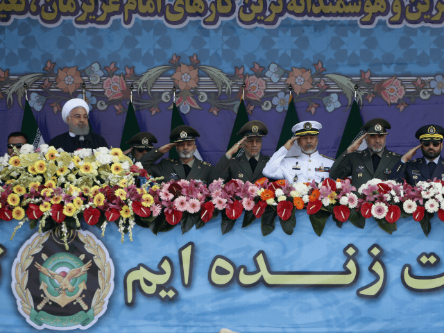 Iranian President Hassan Rouhani (L) and senior members of his armed forces watch a parade on the occasion of the country's annual army day on April 18, 2018, in Tehran. / AFP PHOTO / ATTA KENARE (Photo credit should read ATTA KENARE/AFP/Getty Images)