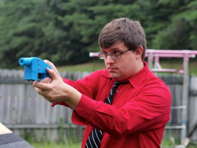 Software engineer Travis Lerol takes aim with an unloaded Liberator handgun in the backyard of his home on July 11, 2013. The Liberator is the first gun that can be made entirely with parts from a 3D printer and computer-aided design (CAD) files downloaded from the Internet. AFP PHOTO / …