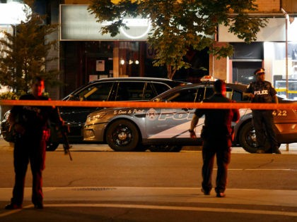 Toronto Police officers walk the scene at Danforth St. at the scene of a shooting in Toronto, Ontario, Canada on July 23, 2018. - A gunman opened fire in central Toronto on Sunday night, injuring 13 people including a child. Two dead incluiding gunman, police reported. (Photo by Cole BURSTON …