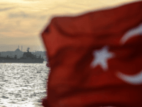 A Turkish flag flies on a ferry as Russian warship the BSF Saratov 150 sails through the Bosphorus off Istanbul en route to the eastern Mediterranean sea on September 26, 2015. AFP PHOTO/OZAN KOSE (Photo credit should read OZAN KOSE/AFP/Getty Images)