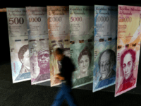 A man walks past banners showing banners depicting Venezuela's currency, the Bolivar, at the Central Bank of Venezuela (BCV) in Caracas on January 31, 2018. Venezuelan President Nicolas Maduro signed the proposal of a new digital currency called 'Petro' to try to combat the economic crisis. / AFP PHOTO / …