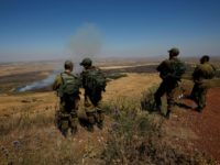 Israeli soldiers in the Israeli-annexed Golan Heights look out across the southwestern Syrian province of Quneitra on July 7, 2018