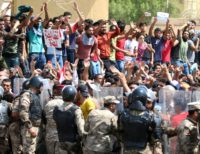 Iraqi riot police line up as protesters chant slogans and hold up signs during a demonstration in Basra on July 15, 2018