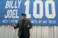 Billy Joel poses under a banner at a press conference to celebrate his achievement of 100 performances at Madison Square Garden in New York