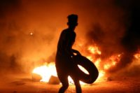 A demonstrator burns tyres during a protest against unemployment and high prices in the southern Iraqi city of Basra during the night of July 12, 2018