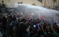 Iraqis waving national flags are being sprayed with water cannon by security forces during a demonstration in the capital Baghdad on July 20, 2018