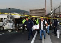 Forensics personnel carry a corpse after a passenger transport vehicle crashed into a truck on a highway outside Mexico City