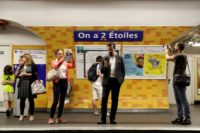 "People took pictures of the new sign reading ""On a deux etoiles"" (""We have two stars"") at Etoile metro station"