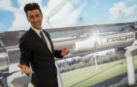 Bibop Gresta (pictured in front of a rendering of a hyperloop project) plans to build a 10-kilometre test track in southwest China
