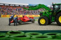All over: A tractor lifts the Ferrari of Sebastian Vettel off the track