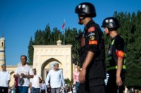 Police patrol as Muslims leave the Id Kah Mosque in the old town of Kashgar in China's Xinjiang Uighur Autonomous Region