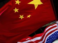 In this Nov. 7, 2012, filephoto, U.S. and Chinese national flags are hung outside a hotel during the U.S. Presidential election event, organized by the U.S. embassy in Beijing. A government report is outlining how spy services from China, Russia and Iran are hard at work trying to steal trade …