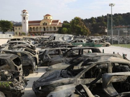 Burned cars are collected together at an old soccer field in Rafina, as clean-up operations get underway following a deadly wildfire in the area east of Athens, Thursday, July 26, 2018. Rescuers intensified a grim house-to-house search Wednesday for more casualties from a deadly forest fire outside Athens, as the …