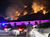 People watch flames from the Holy Fire outside Glen Ivy Hot Springs in Corona, California, southeast of Los Angeles, on August 10, 2018. - Authorities battling massive wildfires in large swathes of California issued mandatory evacuation orders and health warnings Friday over the worsening air quality as the flames grew …