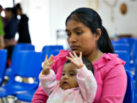 A Guatemalan woman and her infant daughter seeking asylum sit at a Catholic Charities relief center on Sunday, June 17, 2018,