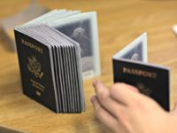 A Passport Processing employee uses a stack of blank passports to print a new one at the Miami Passport Agency