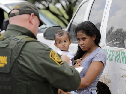 In this Monday, June 25, 2018 file photo, a mother migrating from Honduras holds her 1-year-old child as surrendering to U.S. Border Patrol agents after illegally crossing the border, near McAllen, Texas. As NATO allies convene, one issue not on their formal agenda but never far from their thoughts is …