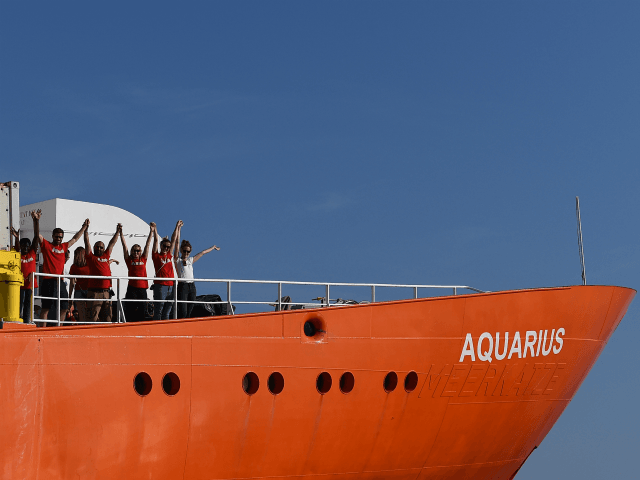 Crew members wave as the rescue ship Aquarius, chartered by French aid group SOS Mediterranee and Doctors Without Borders (MSF), leaves the harbour of Marseille, southeastern France, on August 1, 2018, after having been docked for a month for maintenance work. - The French NGO operating the rescue ship Aquarius, …