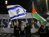 Arab Israelis and their supporters carry a Palestinian (R) and an Israeli flag during a demonstration to protest against the 'Jewish Nation-State Law' in the Israeli coastal city of Tel Aviv on August 11, 2018. The banner in Arabic and Hebrew reads 'justice'. - The controversial law passed last month …