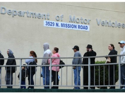 People wait in line outside of the State of California Department of Motor Vehicles (DMV) in Los Angeles, Califor