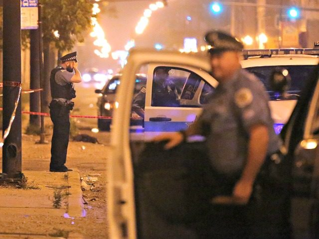 A police officer rests his hand on his forehead at the scene where a 23-year-old man was shot in the face on July 6, 2015, in Chicago.