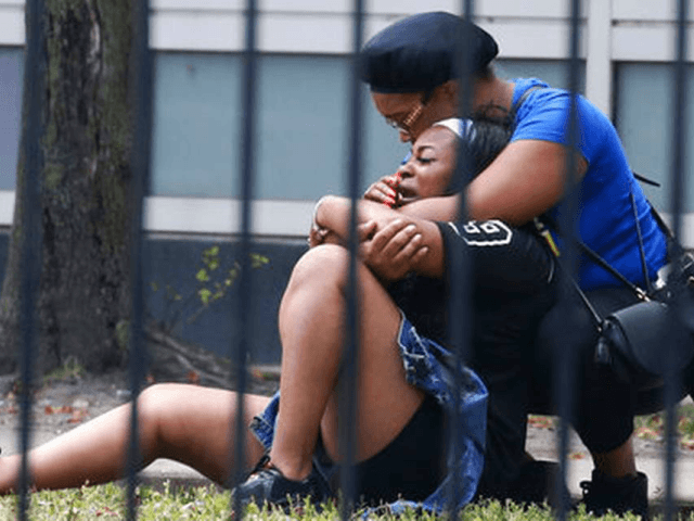 In this Sunday, Aug. 5, 2018 photo, two women cry outside the Stroger Hospital in Chicago after they were asked to leave due to overwhelming crowds of family and friends of shooting victims. Police Superintendent Eddie Johnson plans to discuss the weekend violence during a Monday news conference. (Antonio Perez/Chicago …