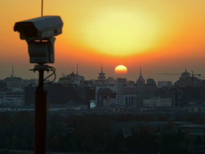 The sun sets behind the Beijing skyline and a security camera, on December 5, 2013. Beijing is the second most expensive city in Asia for expatriates, jumping up the ranking from fifth place last year while Tokyo still tops the list despite a sharply weaker yen, a survey showed. AFP …
