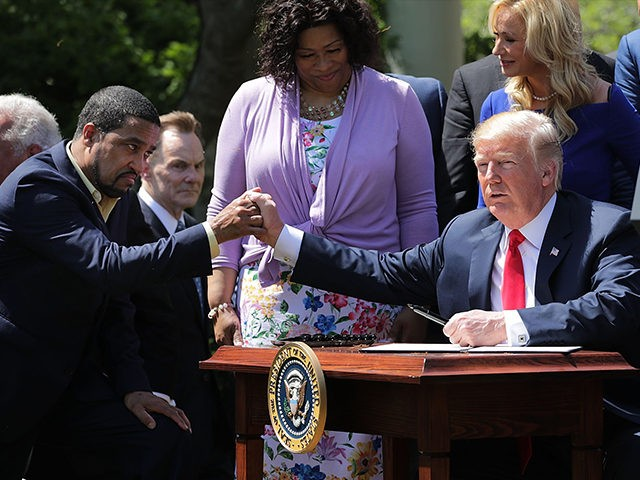 WASHINGTON, DC - MAY 03: U.S. President Donald Trump shakes hands with Pastor Darrell Scott, co-founder of the New Sirit Revival Center, before Trump signs an executive order during an event in the Rose Garden to mark the National Day of Prayer at the White House May 3, 2018 in …