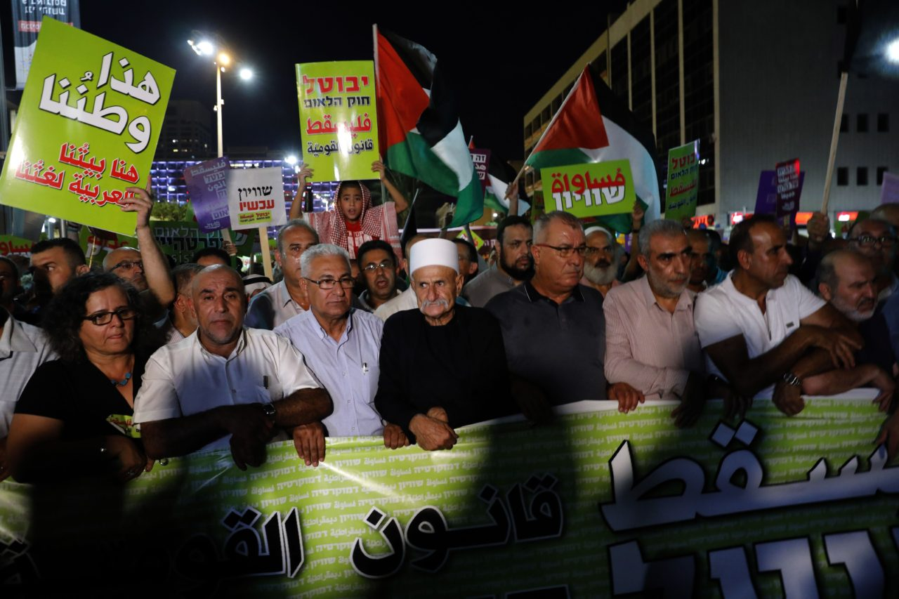 An Israeli Druze man (C) marches with Arab Israelis and their supporters during a demonstration to protest against the 'Jewish Nation-State Law' in the Israeli coastal city of Tel Aviv on August 11, 2018 -