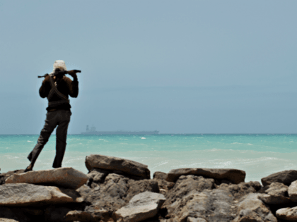 TO GO WITH AFP STORY BY JEAN-MARC MOJON A pirate stands on a rocky outcrop on the coast in Hobyo, central Somalia, on August 20, 2010 as he looks at a hijacked Korean supertanker anchored on the horizon. The Marshall Islands-flagged VLCC Samho Dream is a third of a kilometre …
